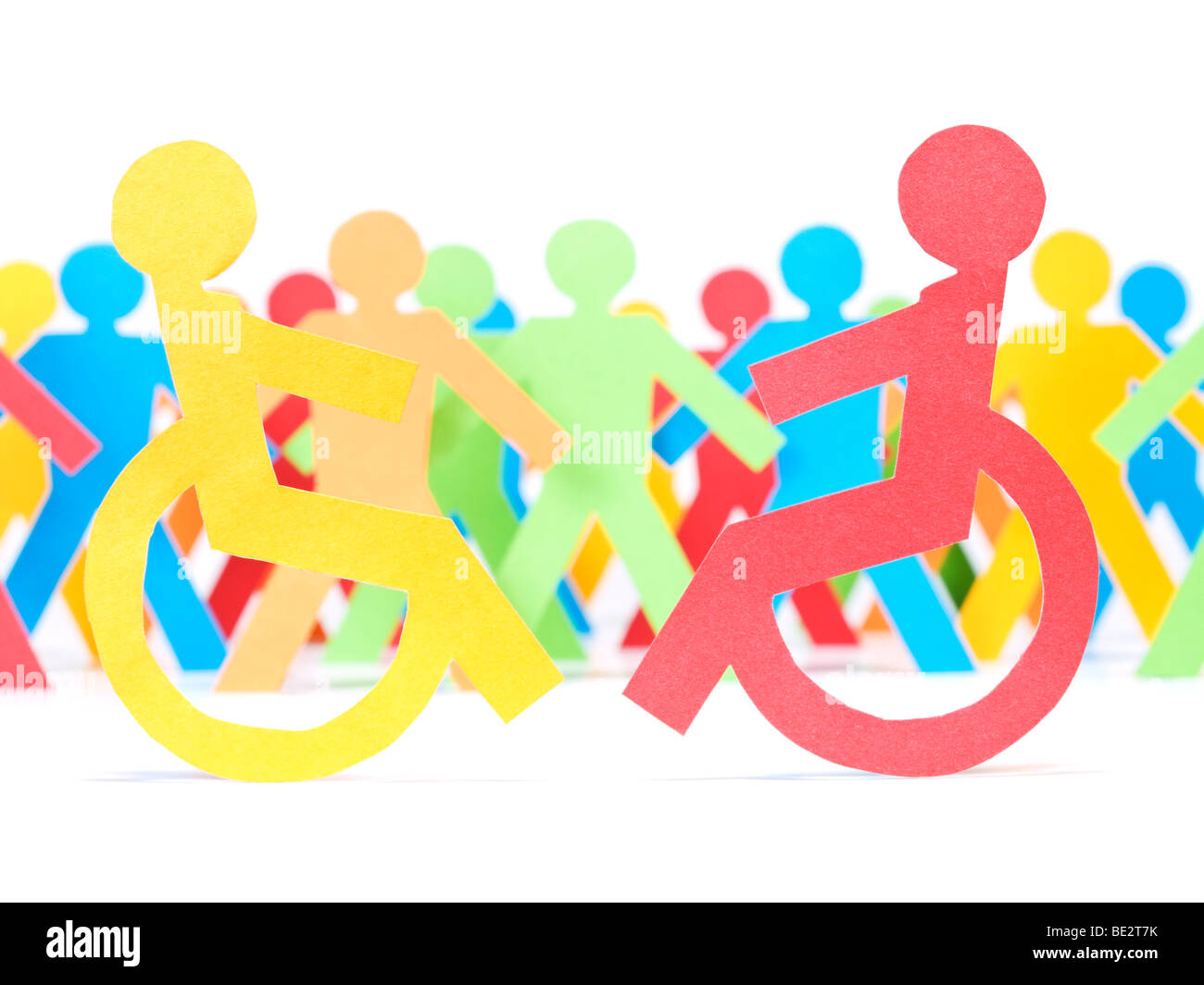 Two paper men on wheelchair. Multicolor paper crew on the background. - Stock Image