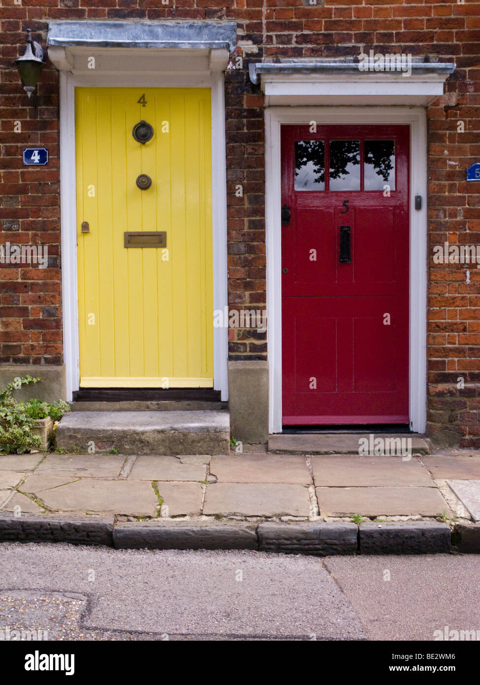 Two painted front doors, one in yellow and one in red, in a row of ...