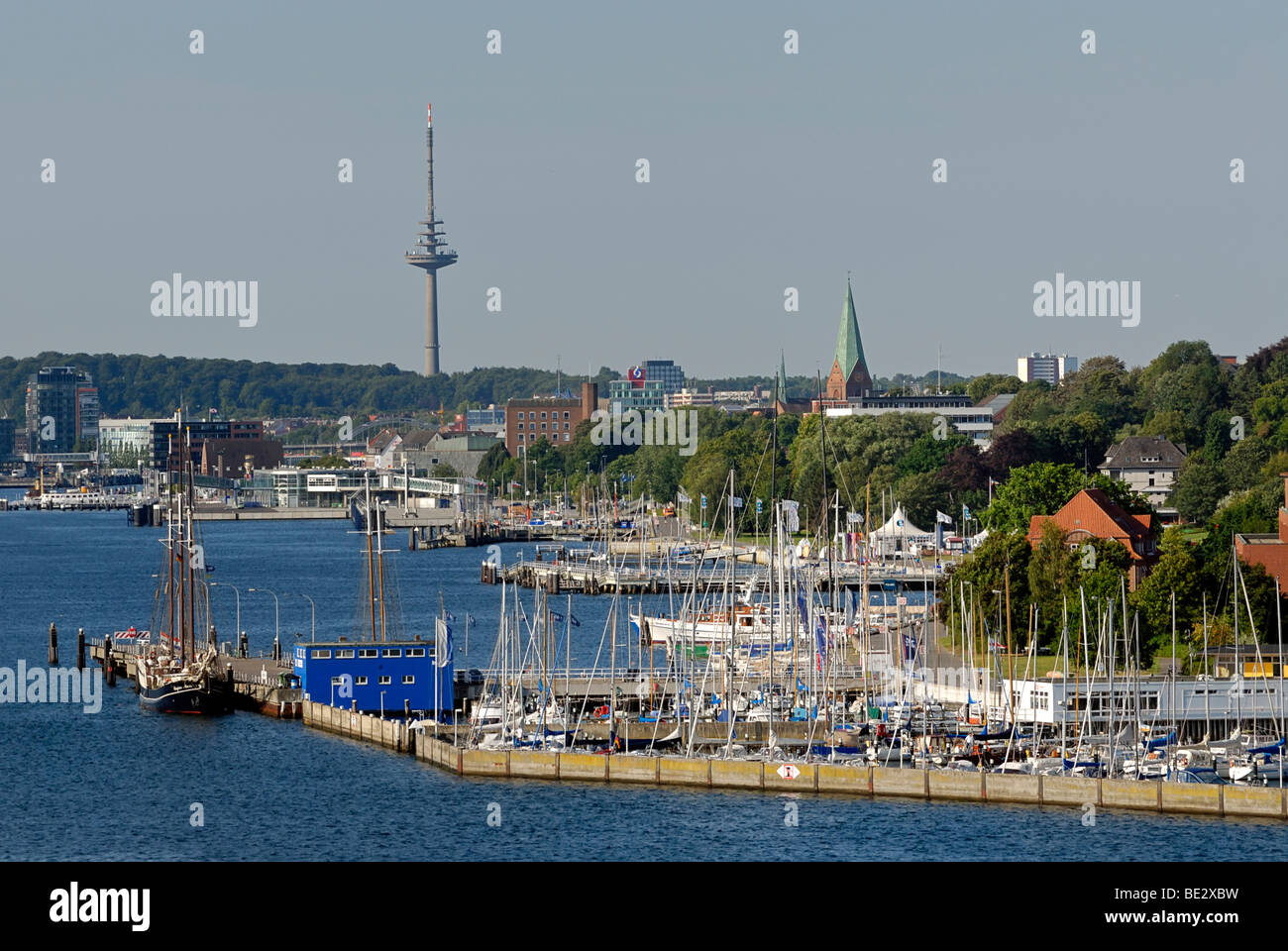 View over the west bank of the inner fjord of Kiel with Duesternbrook Marina, Nikolai Church and the radio tower, - Stock Image