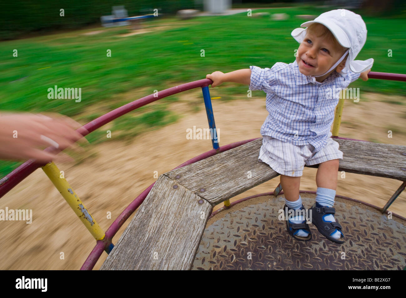 Boy, 18 months, riding a carousel - Stock Image