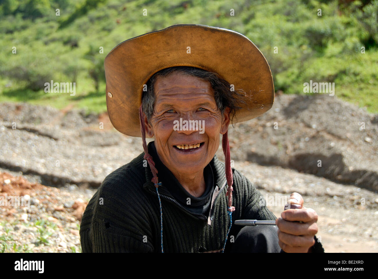 Portrait, ethnology, man of the Mosu ethnicity with hat, smiling and smoking a pipe, Yongning, Lugu Hu Lake area, - Stock Image