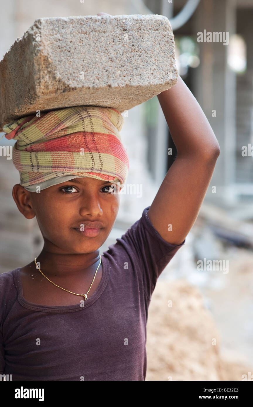 Indian boy labouring on a building site carrying concrete blocks. Andhra Pradesh, India - Stock Image