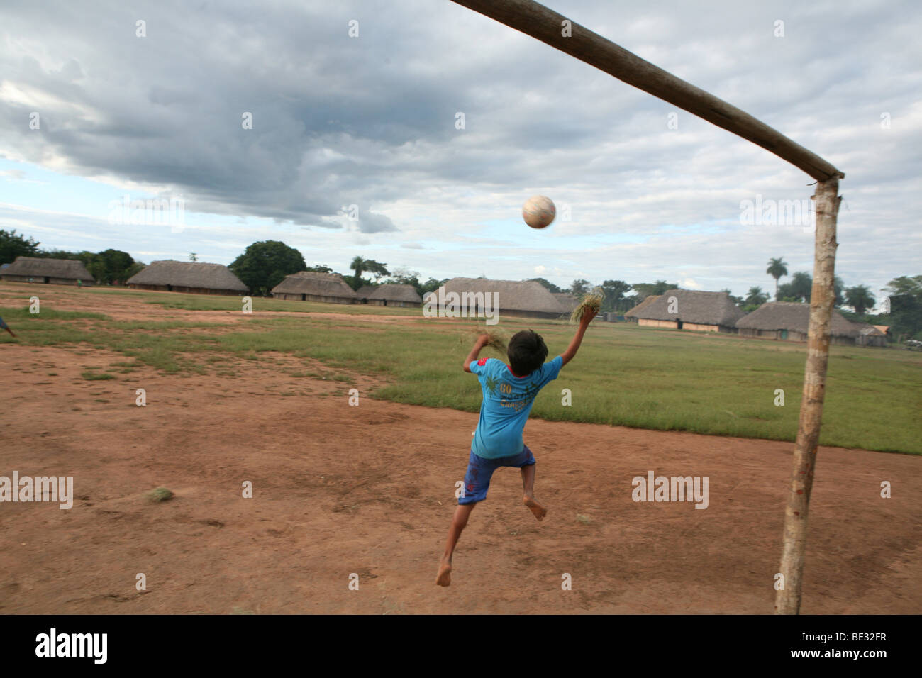 Xingu indians are playing football at the village square. The are participating in the regional football league - Stock Image