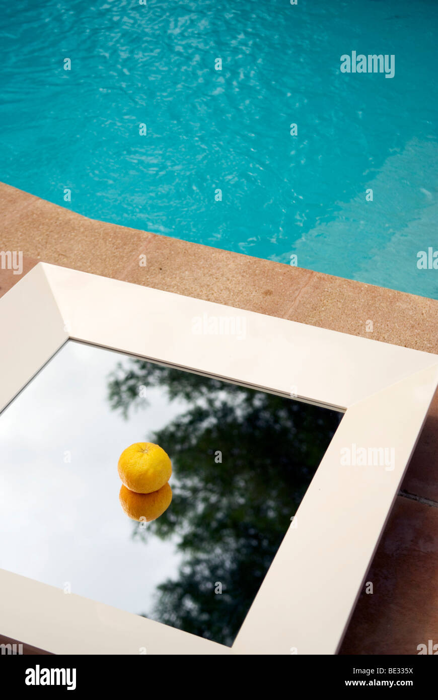 a single tangerine lies in middle of flat white framed mirror by the side of a swimming pool - Stock Image