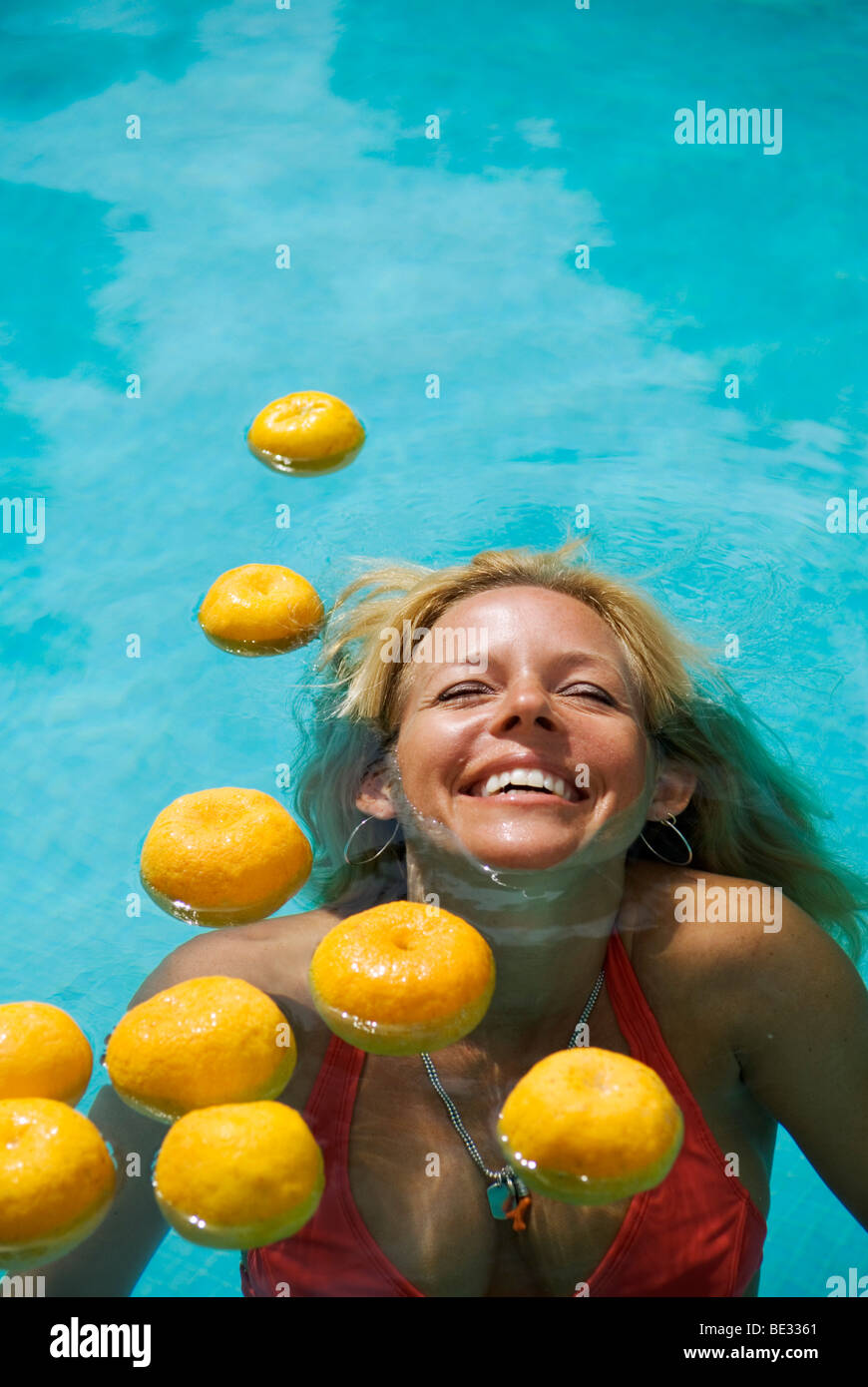 beautiful laughing young woman with long blond hair semi submerged in swimming pool with floating oranges - Stock Image