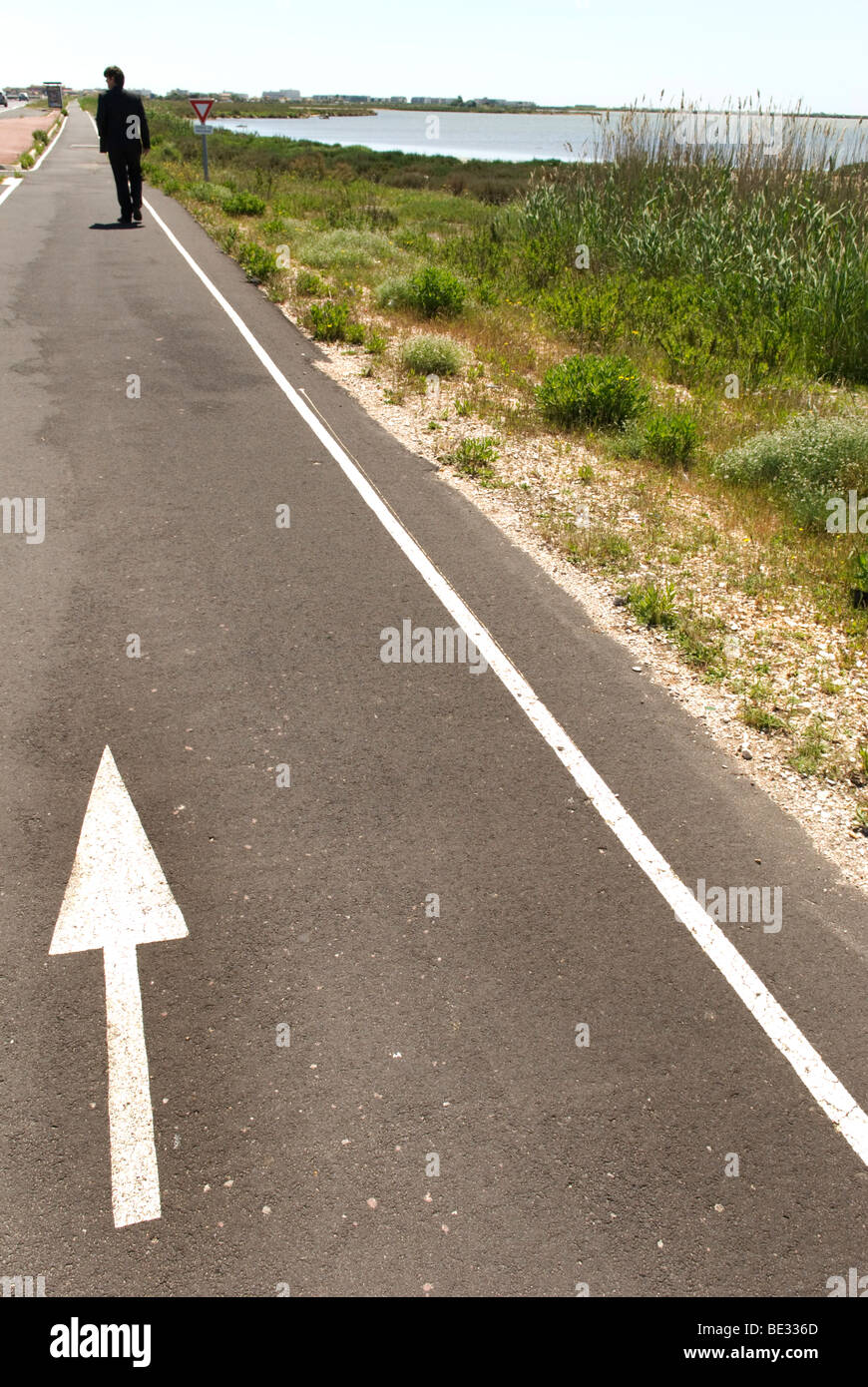 man dressed in dark suit walks away down coastal path with white arrow on it - Stock Image