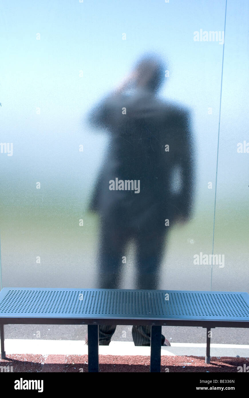 a man in a suit, with his back to us, stands behind frosted glass at a bus stop - Stock Image