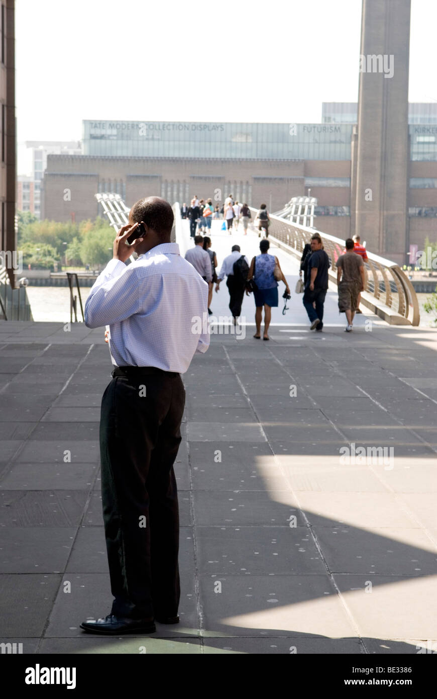 man stands while talking on mobile phone with the millenium bridge and the tate modern in the background - Stock Image