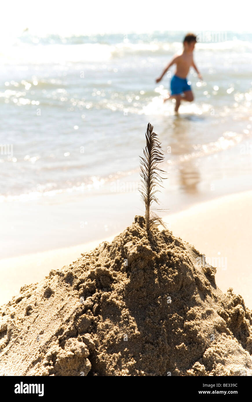 feather stuck in a pile of sand on beach with boy running in sea in background - Stock Image
