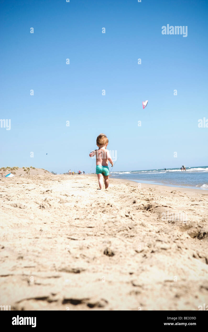 a small male toddler in swimming costume walks away from camera alone on beach with kites overhead - Stock Image