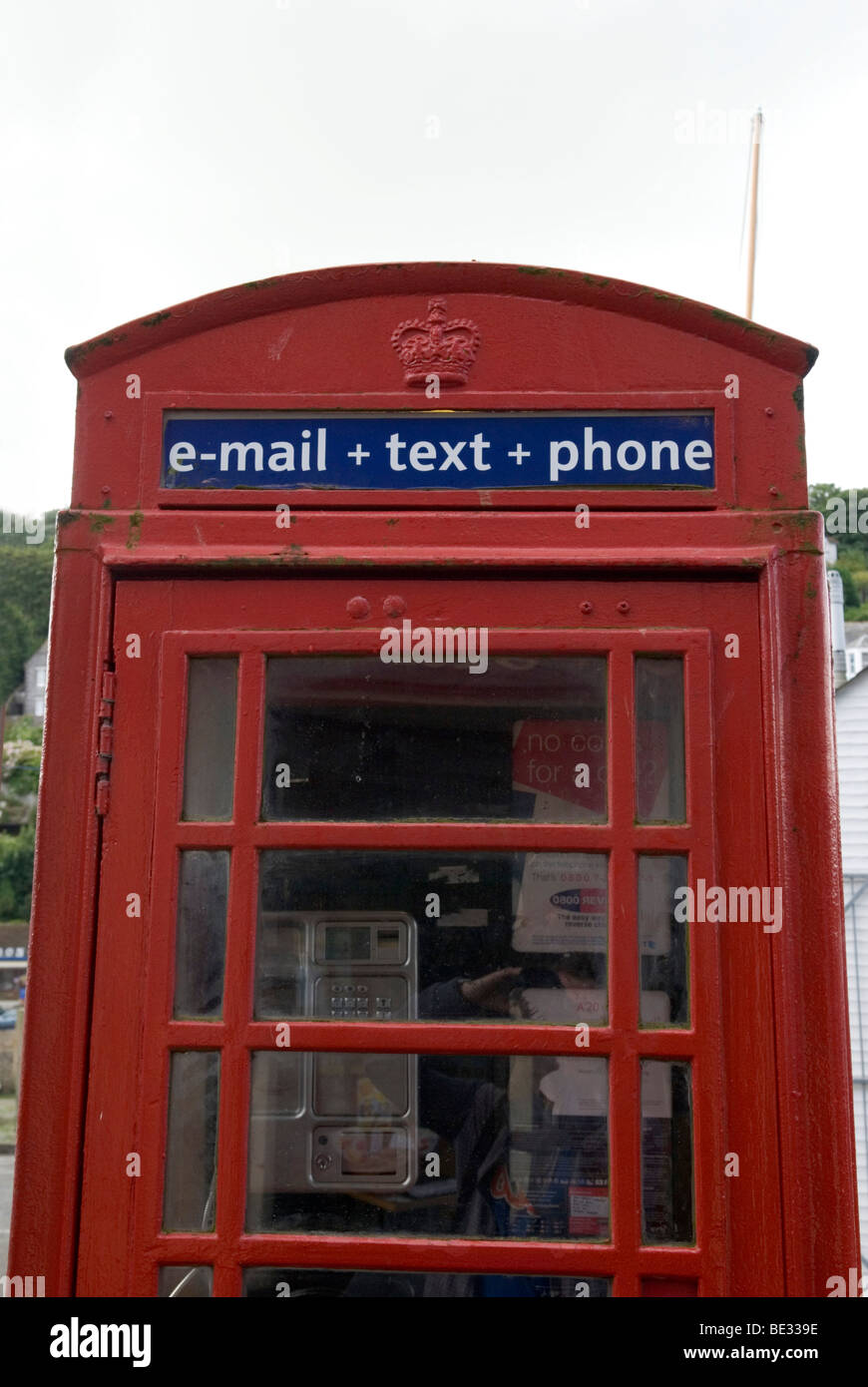 close up of old style british red phone box with the phrase 'e-mail+ text + phone' stuck over door on blue - Stock Image