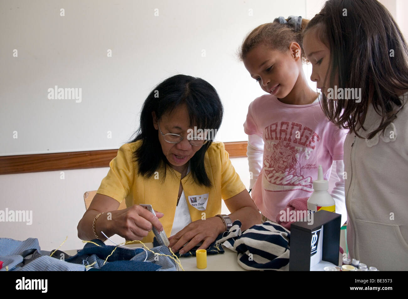 ethnic lady teaching basic of sewing to young girls - Stock Image