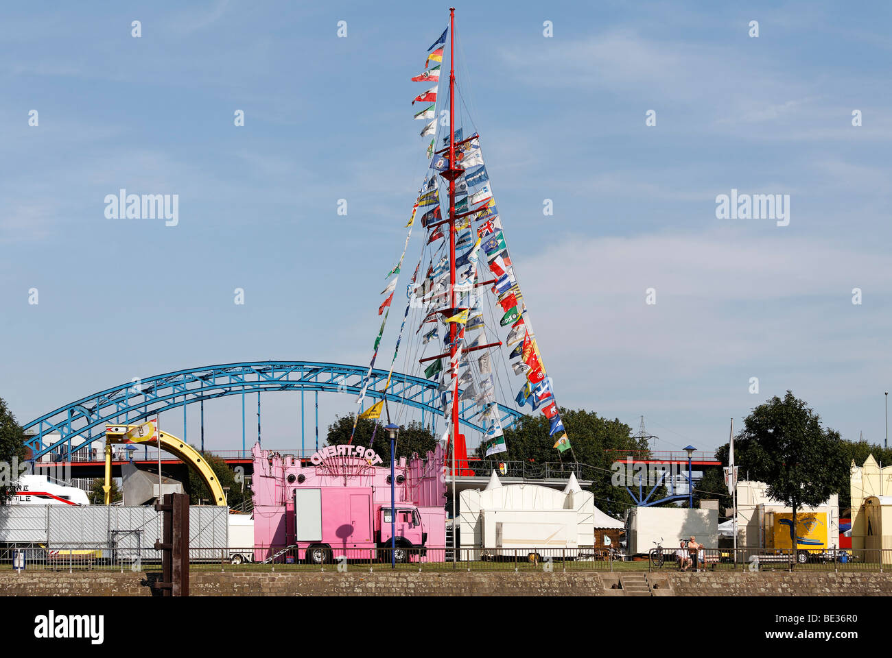 Flagpole with flags of the Duisburg shipping companies, booths of the Ruhrort post festival, Duisburg, Ruhrgebiet - Stock Image