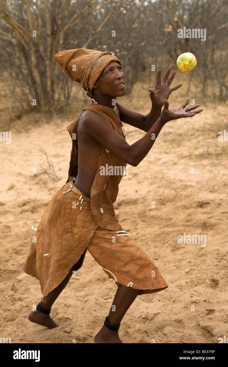 Naro bushman (San) woman playing a ball game with a wild melon, Central Kalahari, Botswana - Stock Image