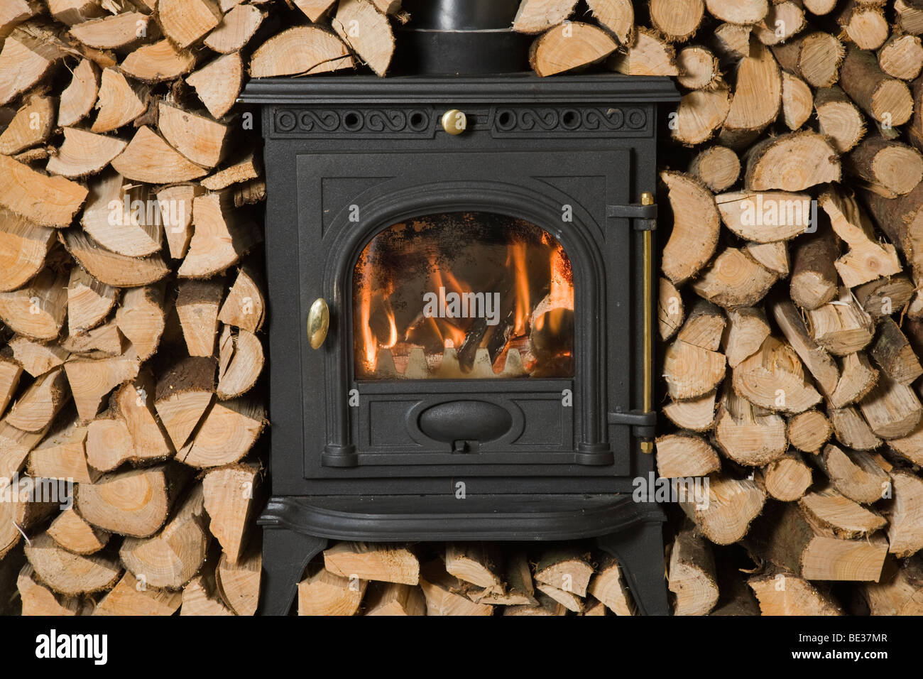 Wood burning stove surrounded by chopped and stacked firewood ready for burning - Stock Image