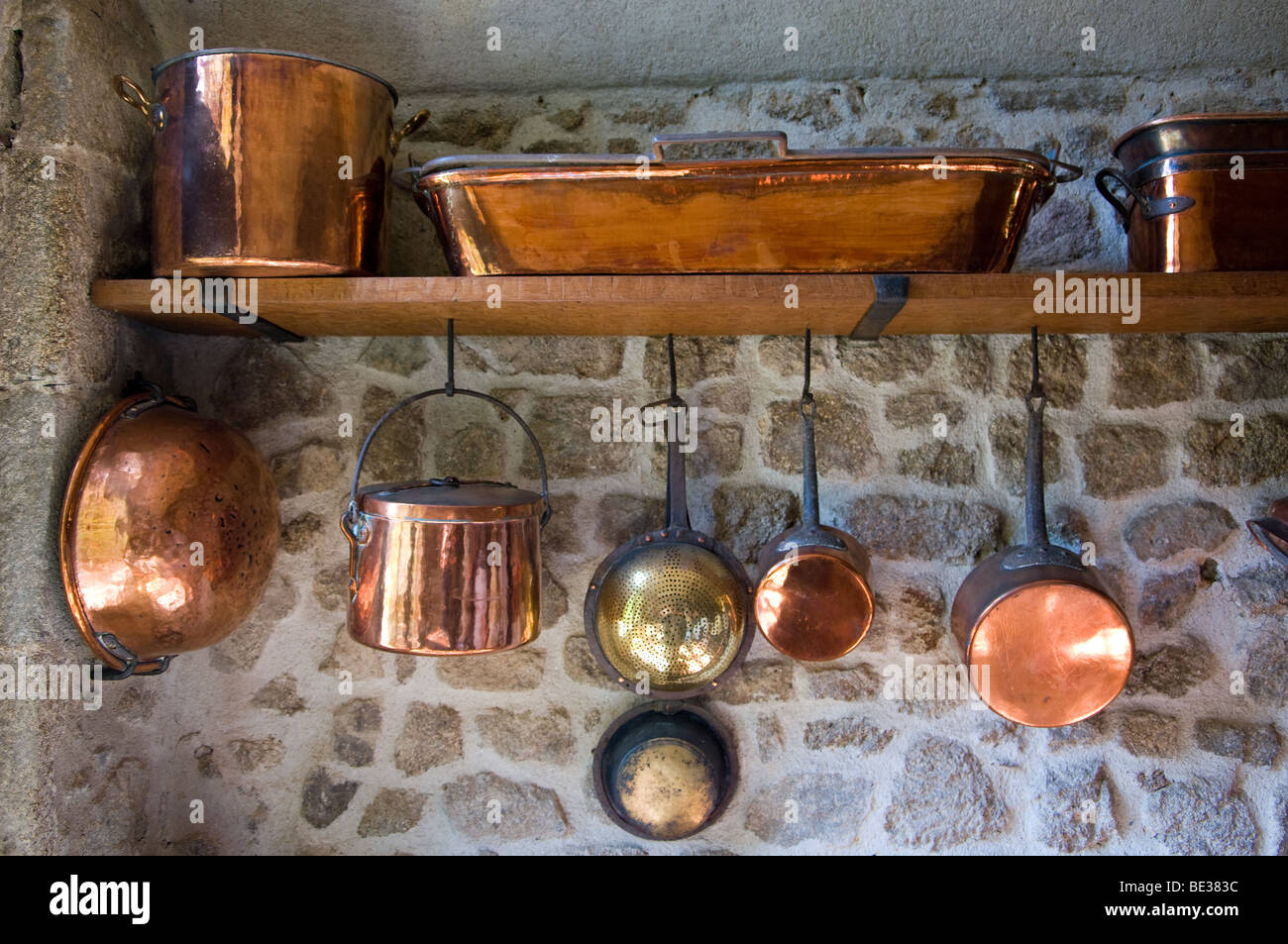 A range of brass pots and pans in a French chateau kitchen Stock Photo