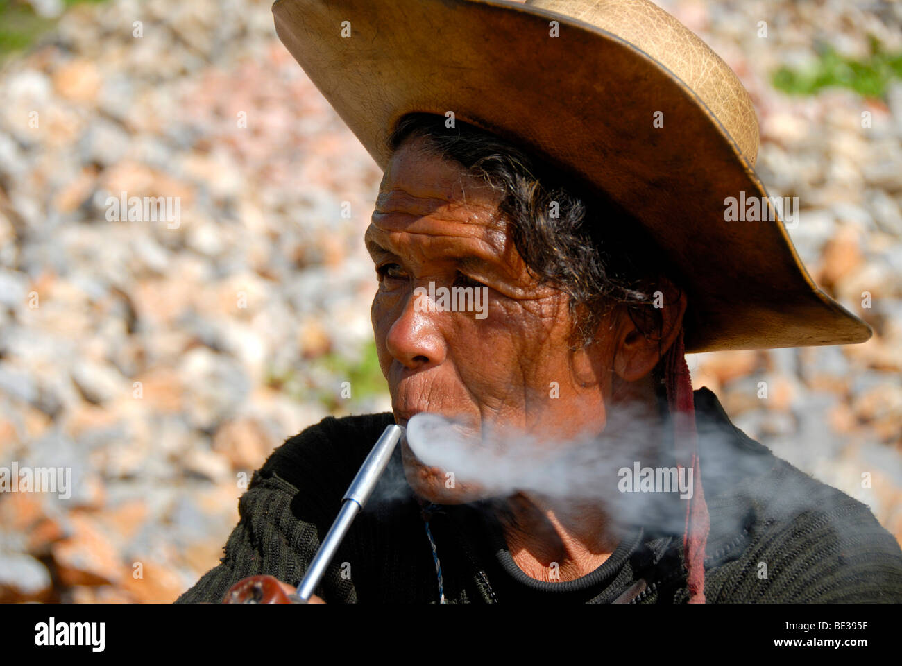 Portrait, ethnology, man of the Mosu ethnicity with hat, smoking a pipe, Yongning, Lugu Hu Lake area, Yunnan Province, - Stock Image
