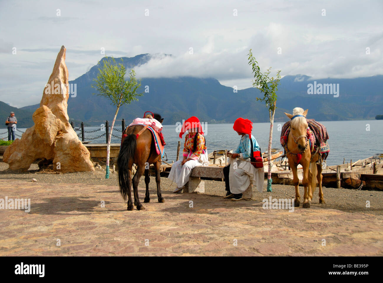 Ethnology, women of the Mosu ethnicity dressed in traditional costumes with horses on the shore, Luoshui, Lugu Hu - Stock Image
