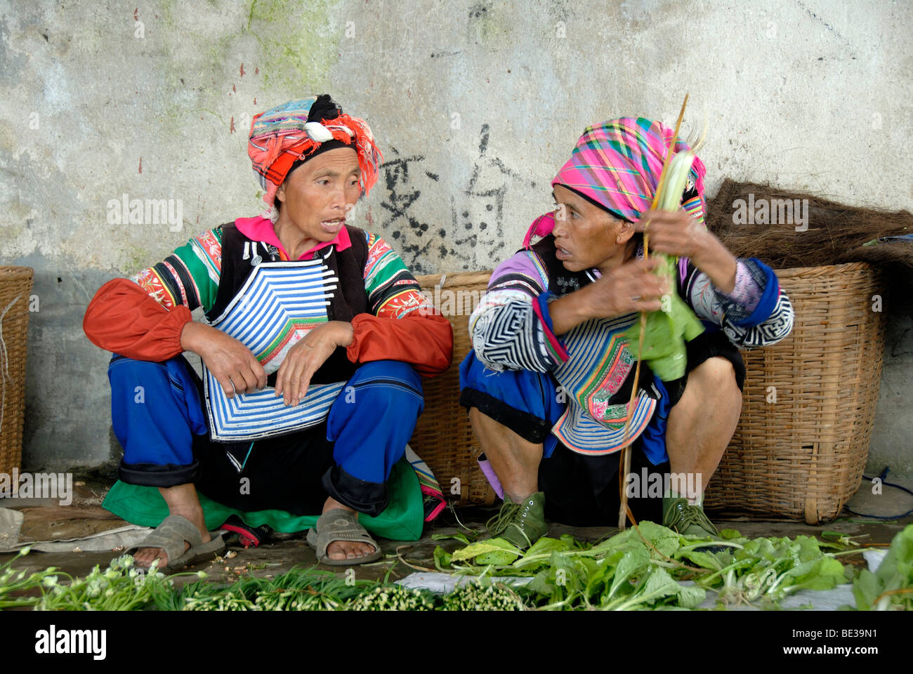 Ethnology, two market women of the Yi ethnic group squat deep in conversation, colorful clothes, Xinji, Yuanyang, - Stock Image