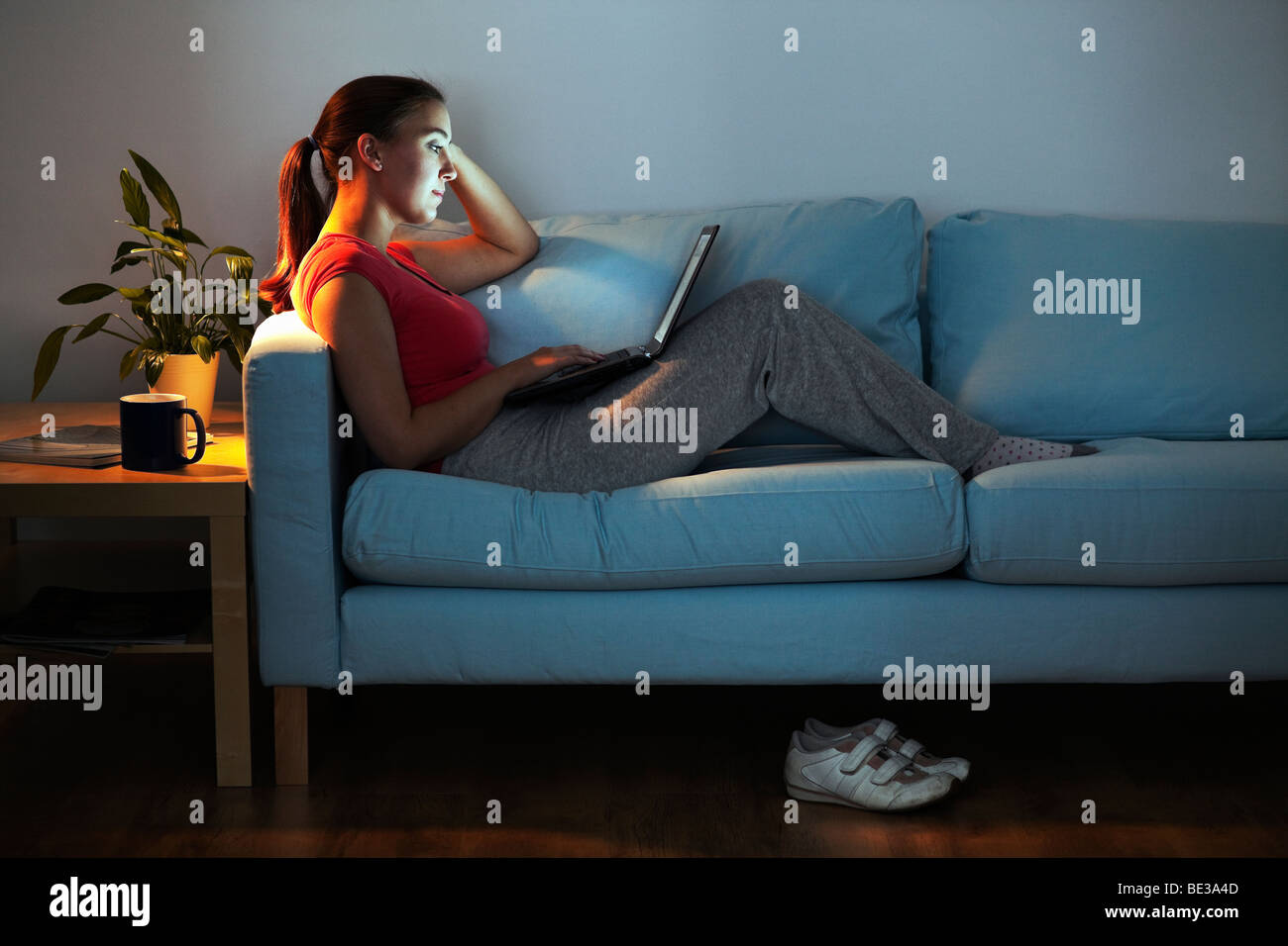 Young woman on sofa with laptop - Stock Image