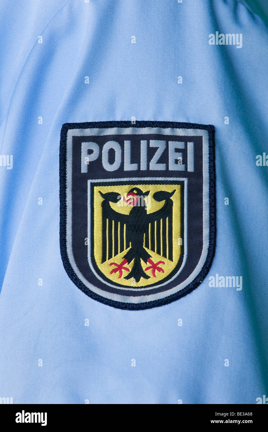 Police badge with federal eagle on sleeve of a blue shirt - Stock Image