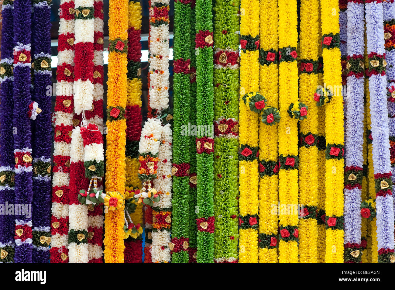 Imitation flower garlands used in Hindu religious worship on a market stall in India - Stock Image
