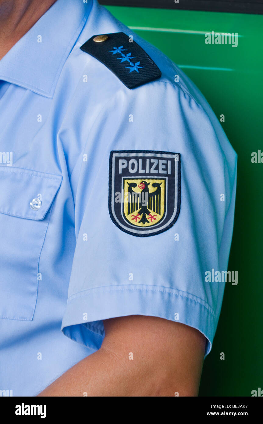 German policeman, epaulette of a police seargent, below it emblem of the Federal police, on the sleeve of a blue - Stock Image