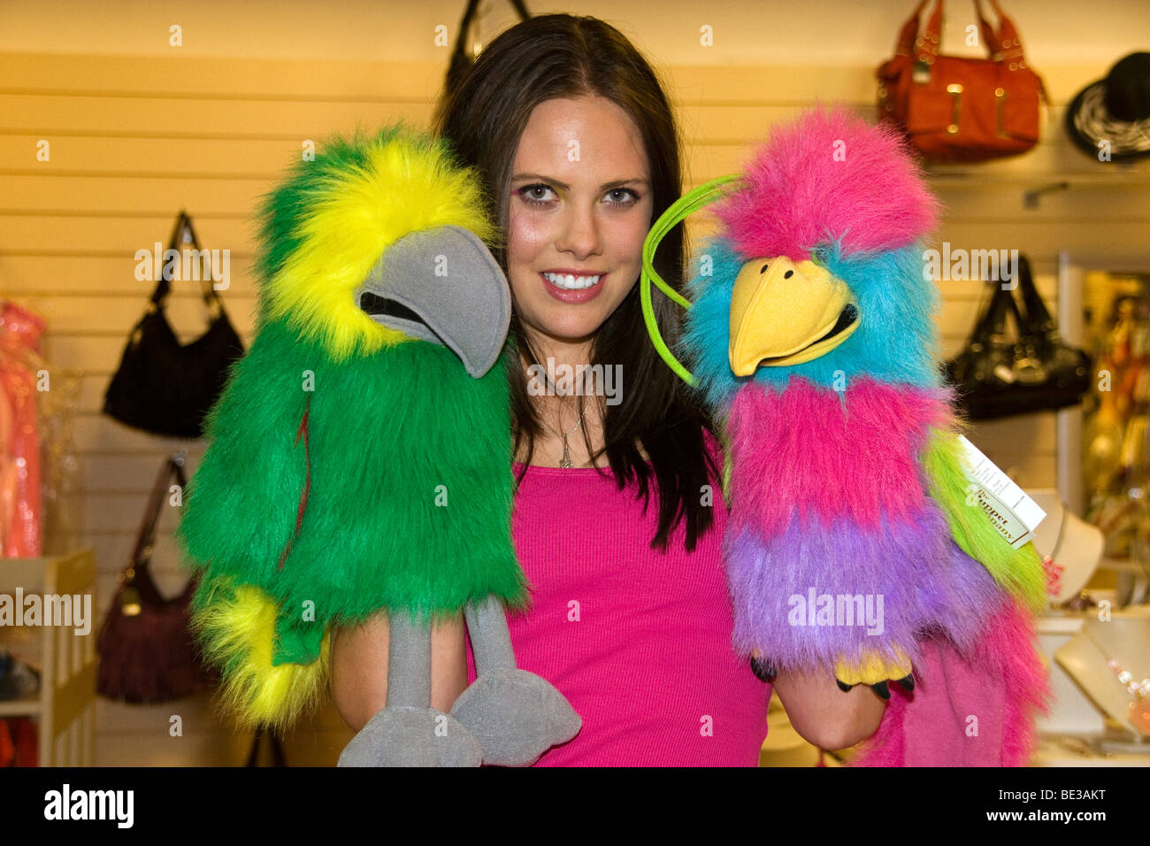 Glamourous female playing with two colourful hand held parrot puppets inside a Dundee Boutique store Stock Photo