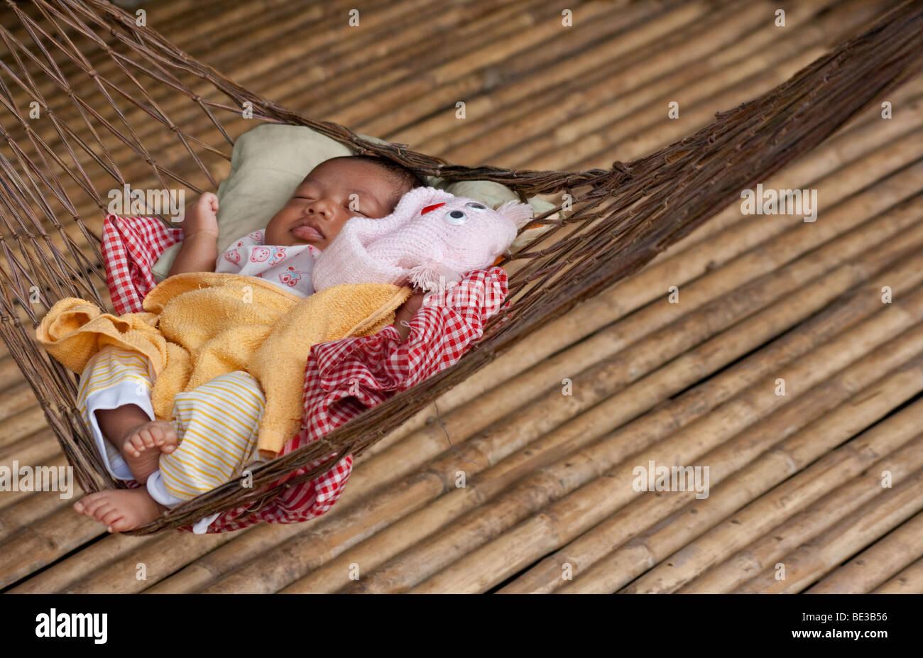 Young Cambodian baby sleeping in hammock, Kampong Chhnang, Cambodia Stock Photo
