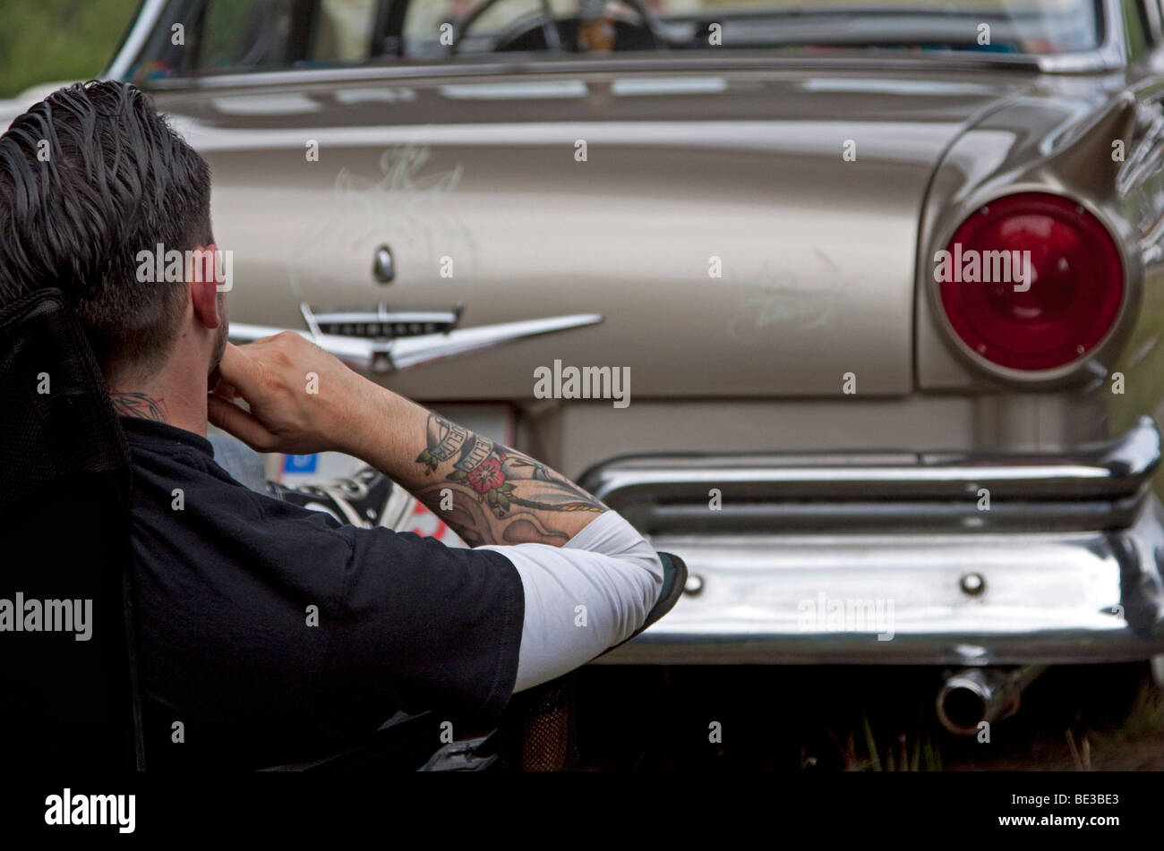 Man sitting in front of the rear of his vintage car Stock Photo