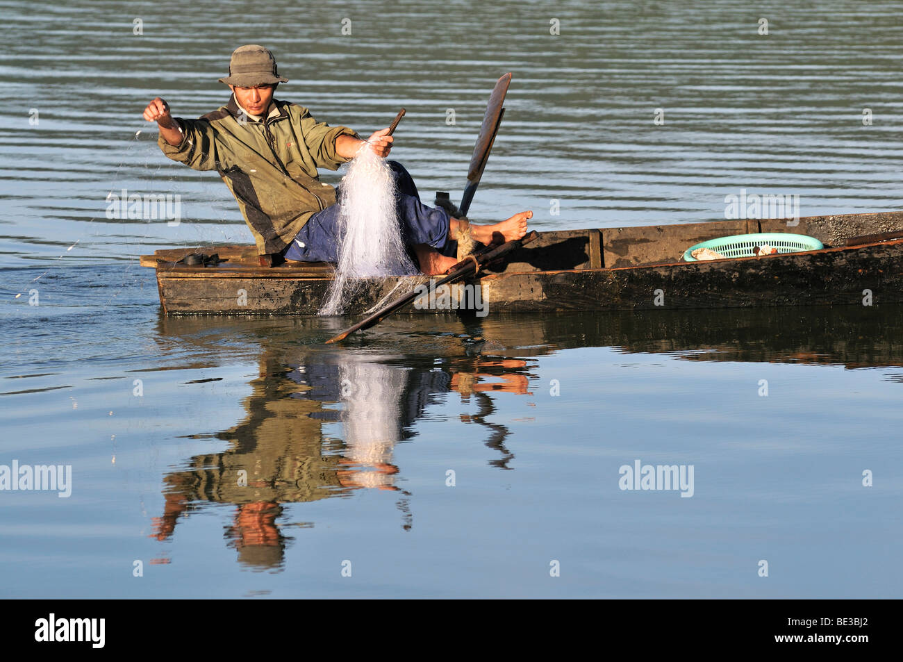 Fishermen in a wooden boat pulls out a net on Tuyen Lam lake, Dalat, Central Highlands, Vietnam, Asia - Stock Image