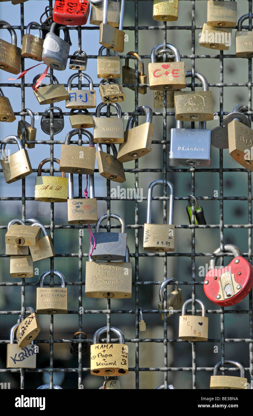 Padlocks as a sign of friendship and love at the metal fence of the Hohenzollernbruecke Hohenzollern Bridge in Cologne, - Stock Image
