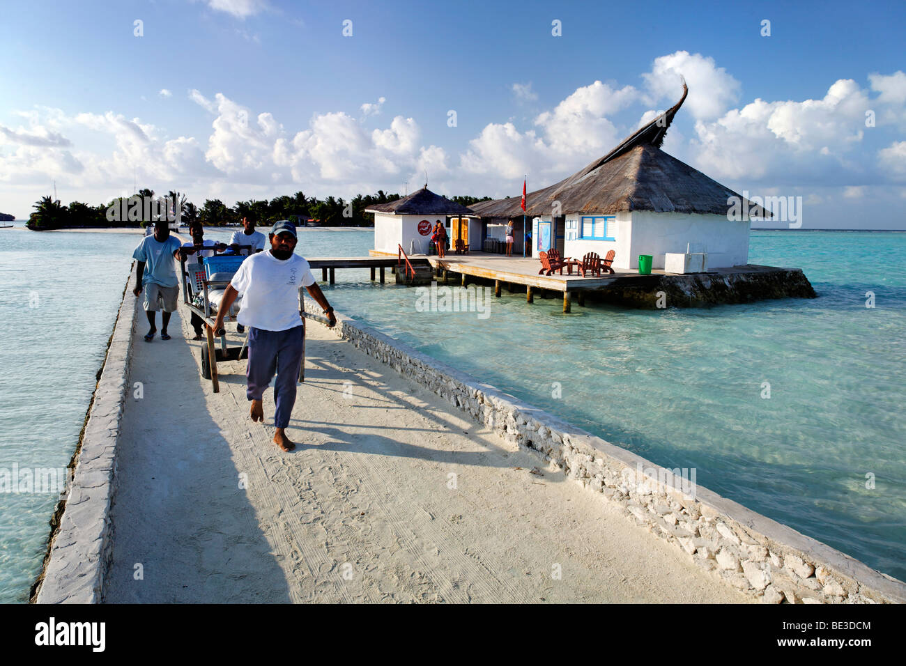 Maldivians at a jetty carry aluminium diving tanks, Maldive island, South Male Atoll, Maldives, Achipelago, Asia, - Stock Image