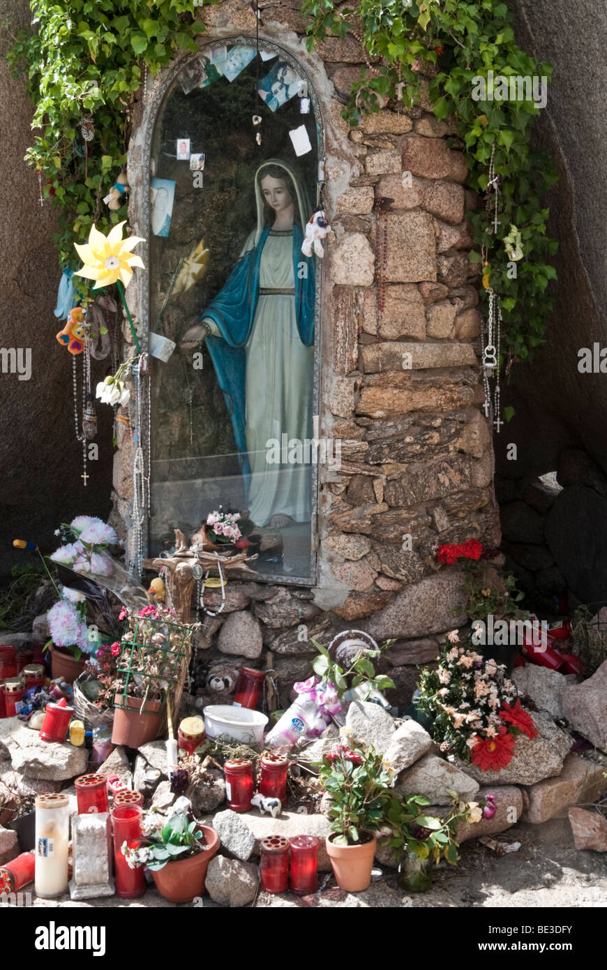Roadside shrine with statue of Virgin Mary and offerings in northern Sardinia, Italy - Stock Image