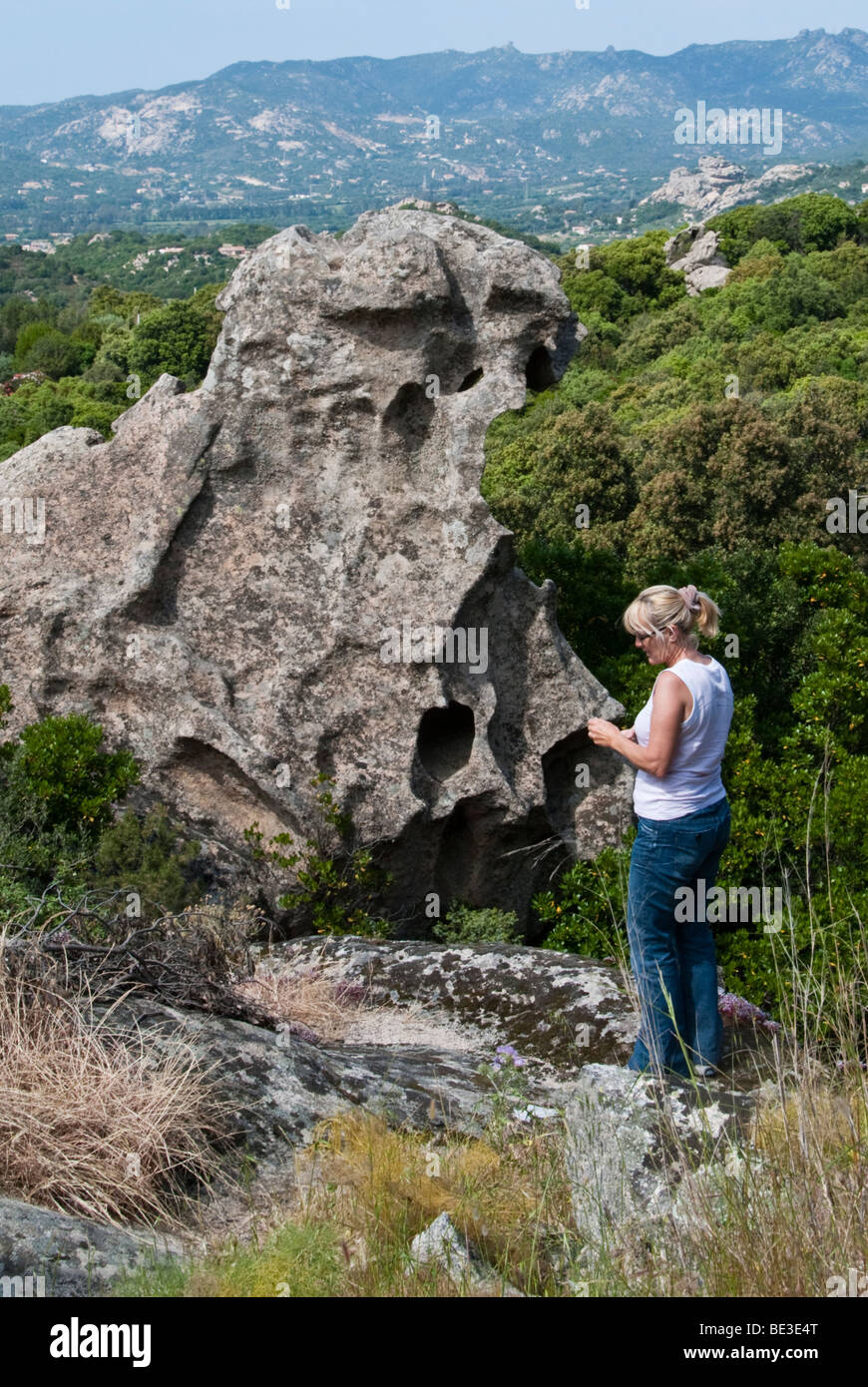 Tourist taking a photograph close to a jagged rock in northern Sardinia, Italy - Stock Image