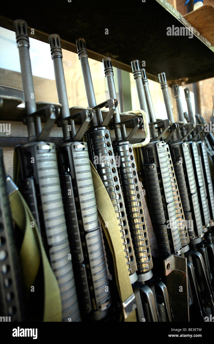 Assault rifles stand ready on the weapons rack. - Stock Image
