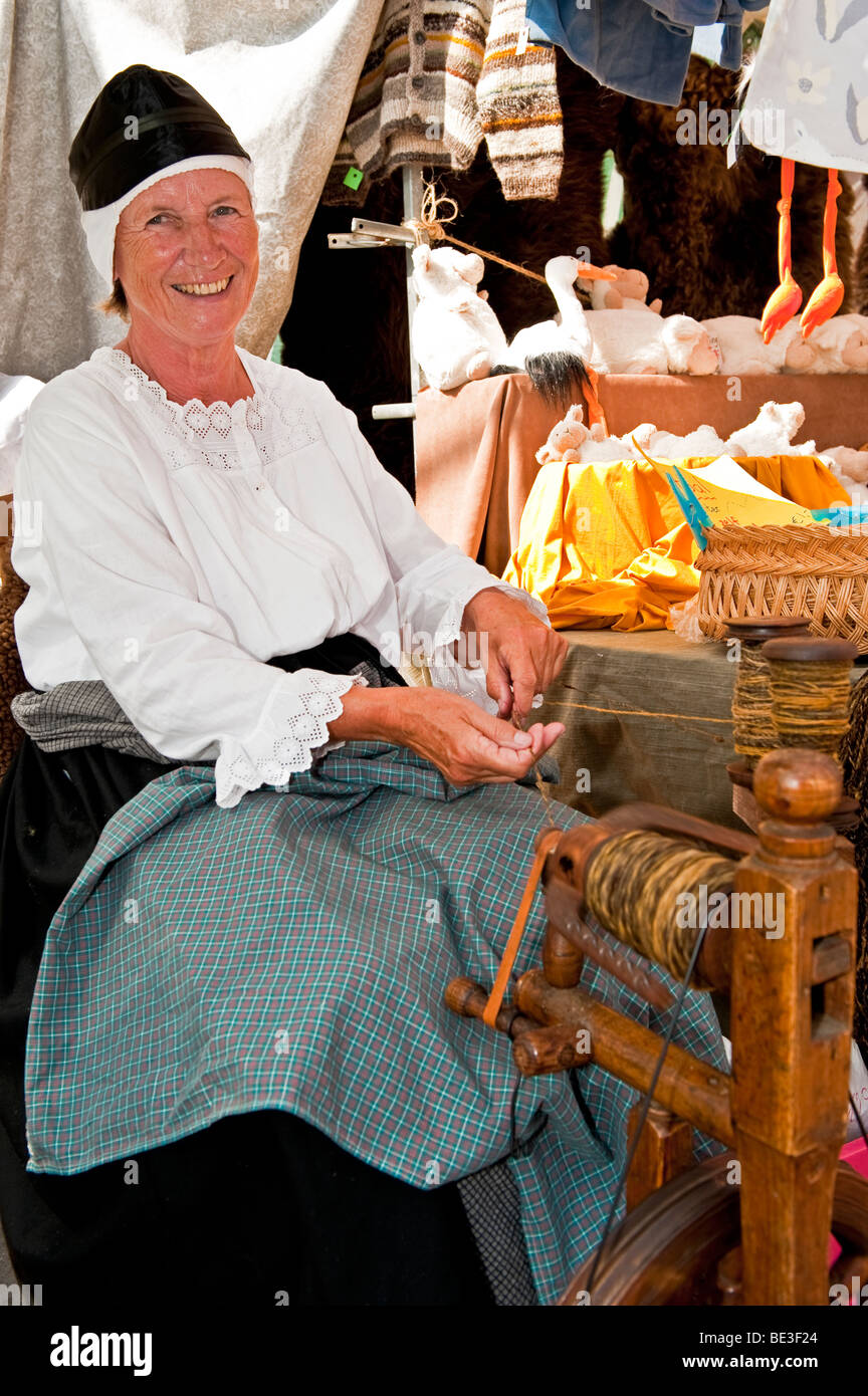 A lady using a spinning wheel Stock Photo
