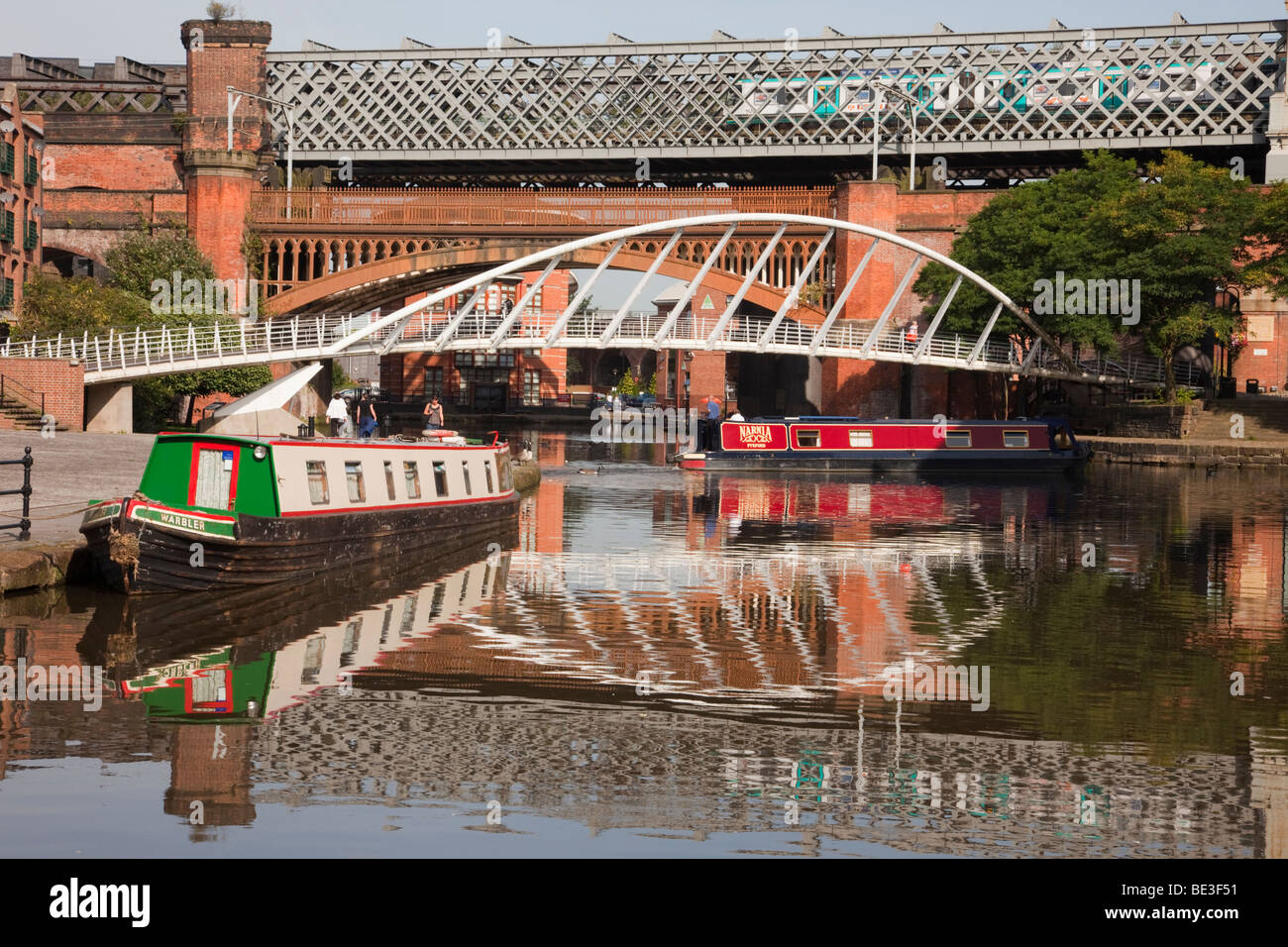 The Bridgewater Canal basin reflecting narrowboats and Merchants Bridge in conservation area. Castlefield Urban - Stock Image