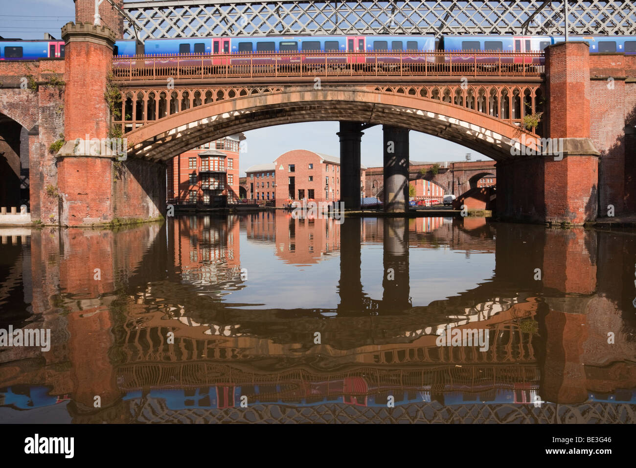 Train crossing Victorian railway viaduct bridge over Bridgewater Canal in Castlefield Urban Heritage Park conservation - Stock Image