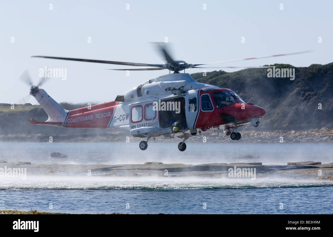 Coastguard rescue helicopter landing on rocky beach to aid an injured tourist at Kimmeridge Bay, Dorset, UK - Stock Image