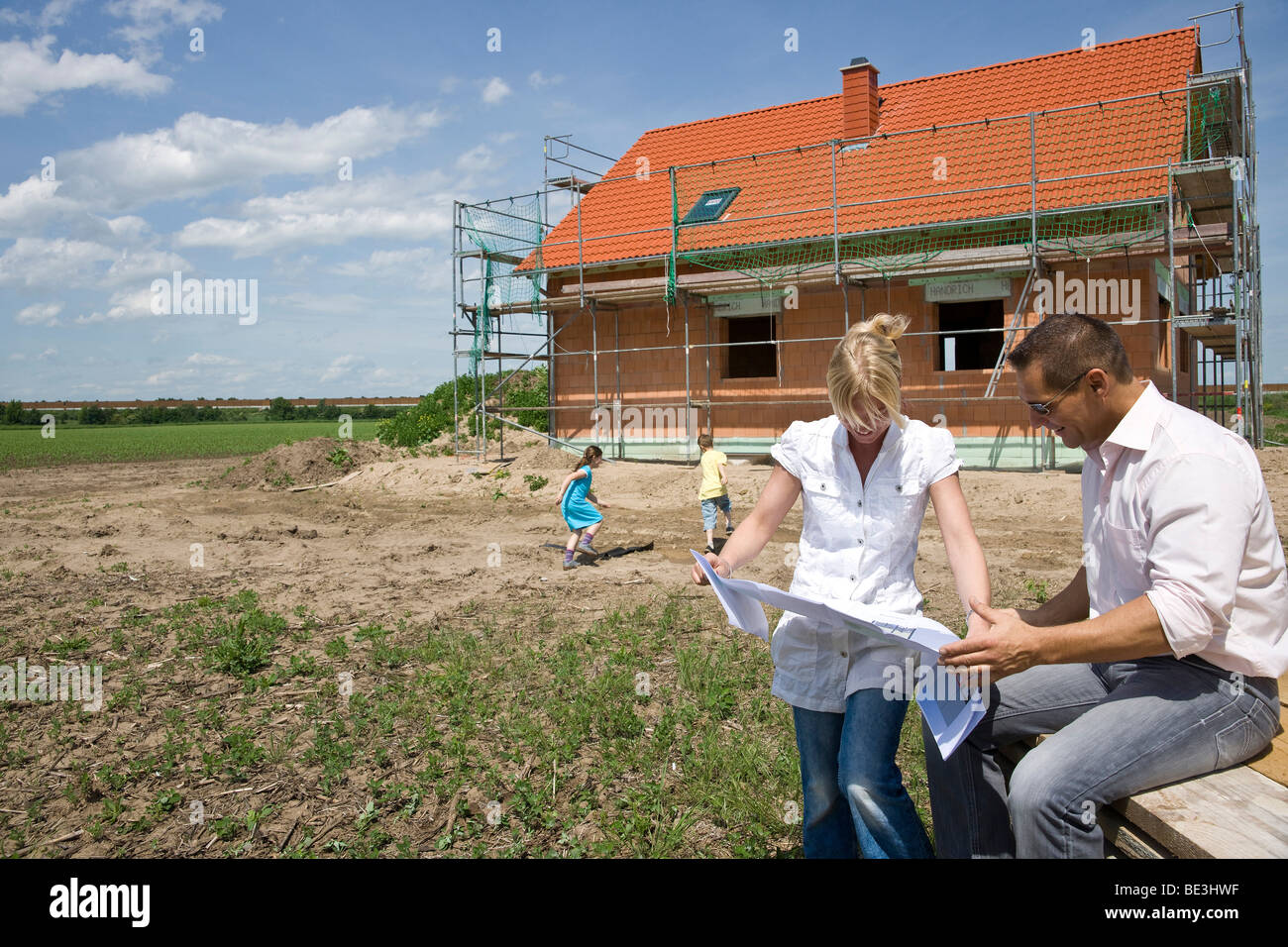 Married couple in front of their future home, looking at the construction plan Stock Photo