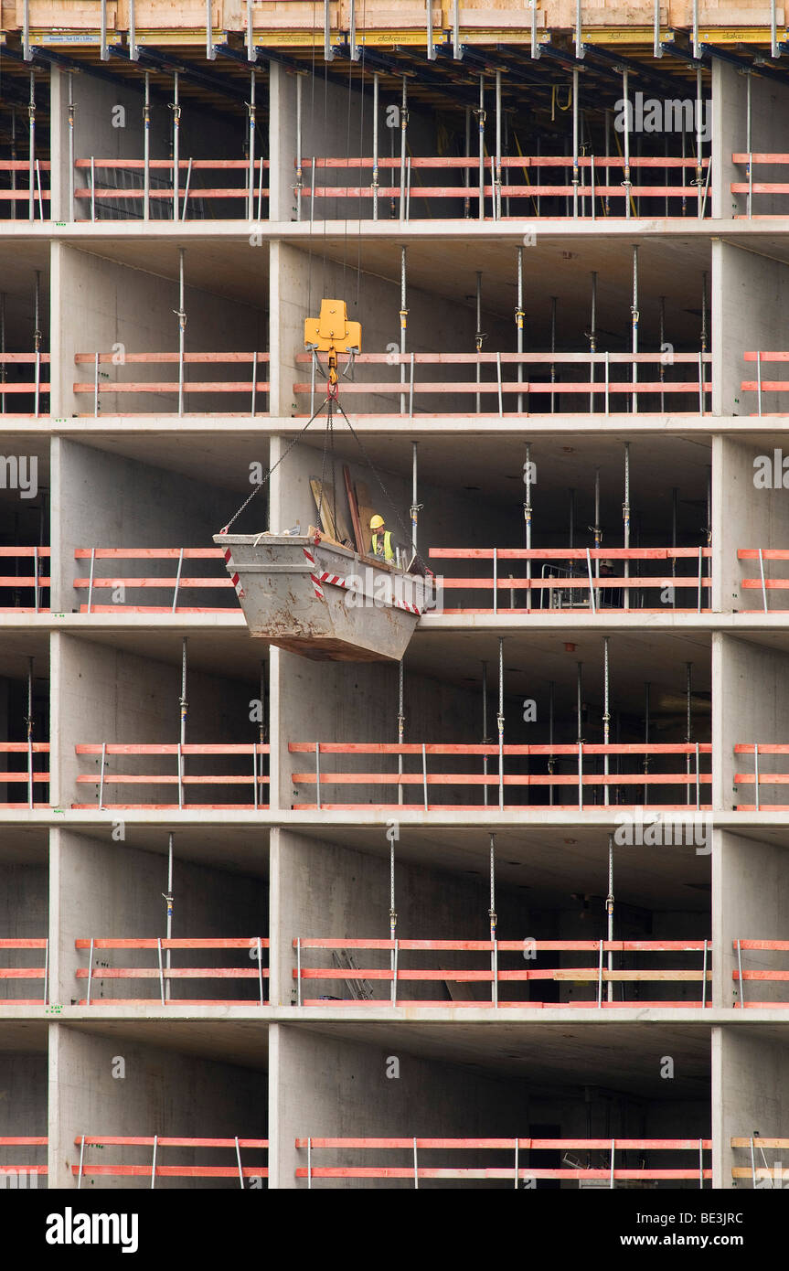 Large construction site, material containers hanging on a crane in front of a building shell is being unloaded, - Stock Image