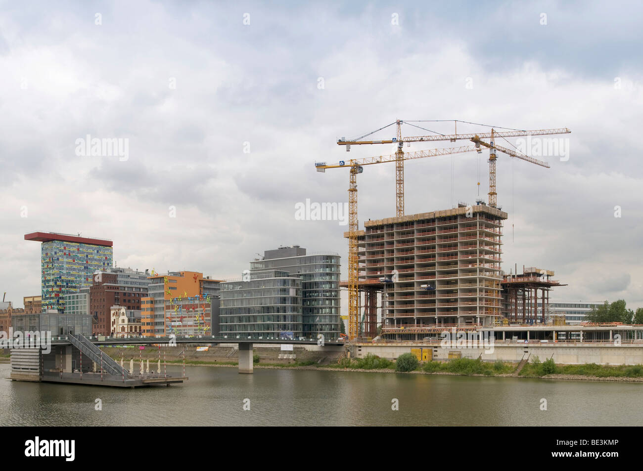 Large construction site Duesseldorf Medienhafen media port, Hotel building shell next to office buildings with 'Flossis', - Stock Image