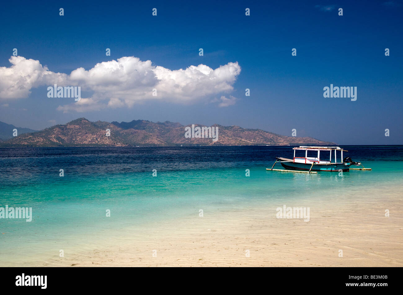 Lonely boat and pristine tropical waters at Gili Air island, Lombok, Indonesia - Stock Image