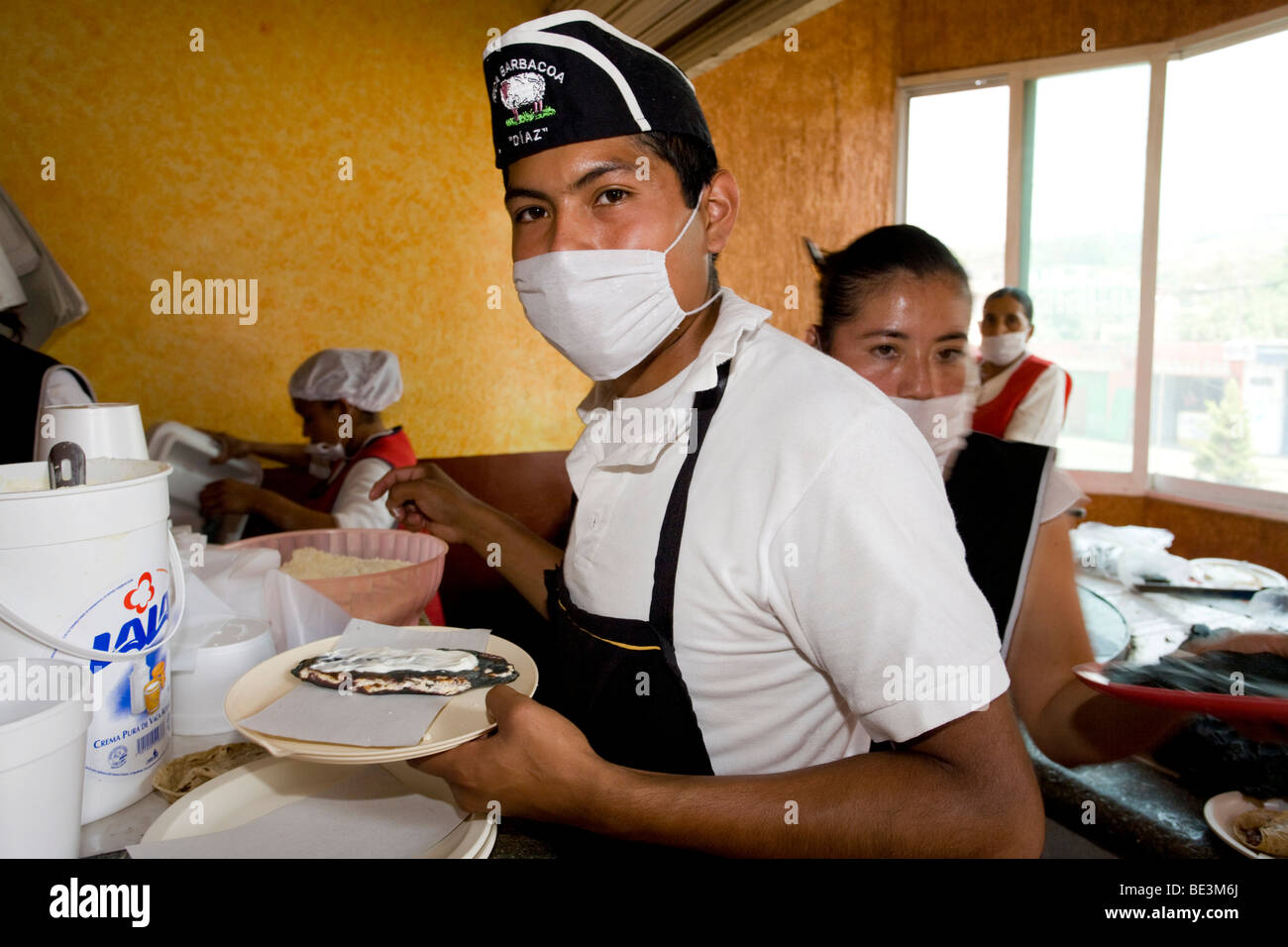 Waiter in a restaurant in Mexico wearing a mask because of the pig flu, H1N1, Cuernavaca, Morelos, Mexico Stock Photo