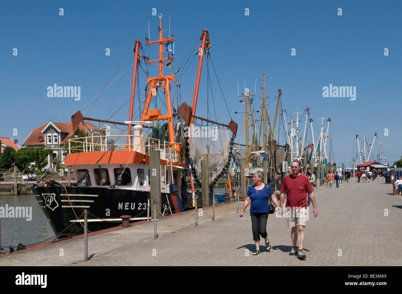 Tourists next to the fleet of shrimp boats in the harbor Neuharlingersiel, North Sea, East Frisia, Lower Saxony, - Stock Image