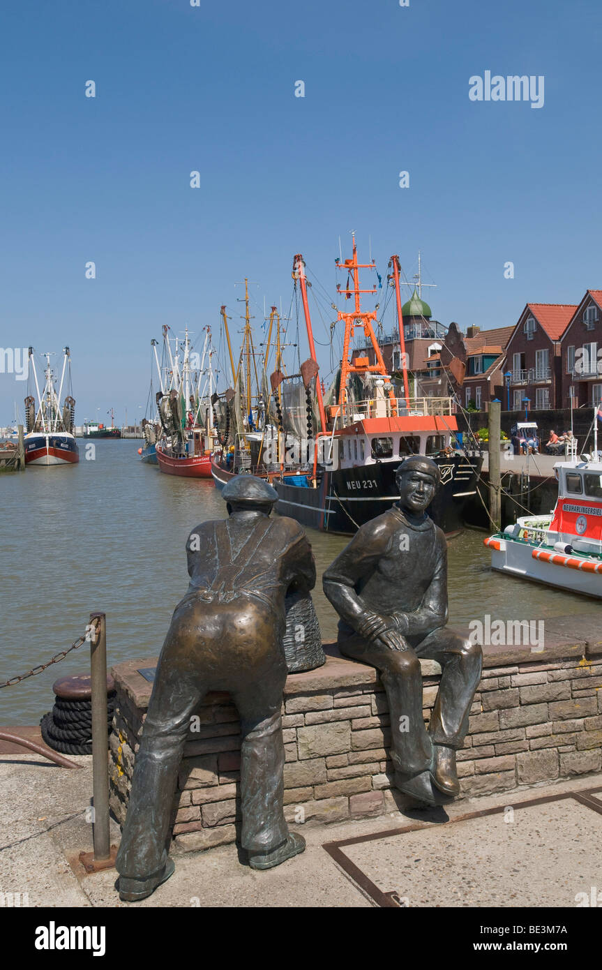 Bronze sculpture by of Old Fisherman and Young Fishermen in the port Neuharlingersiel, in the back shrimp boats, - Stock Image