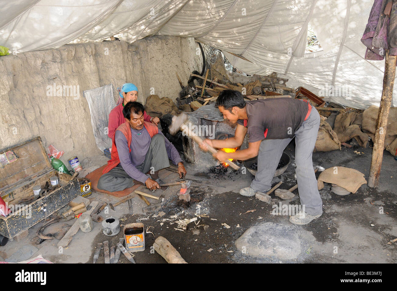 Blacksmith with his wife and assistant manufacturing sickles for the grain harvest in a tent, Shey, Ladakh, India, - Stock Image