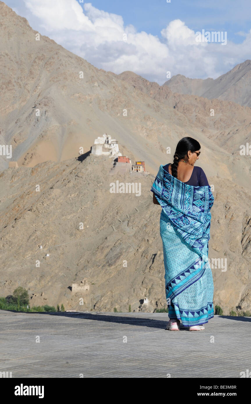 Indian woman as a tourist in the summer holidays above the oasis of Leh with a view on Gonkhang and castle ruins, Stock Photo