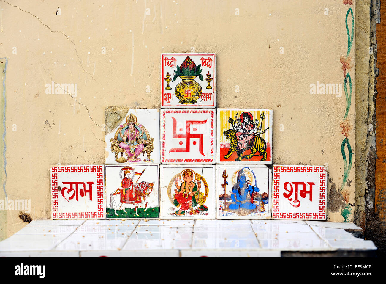 Tiles with Indian, Hindu deities and the Swastika for good luck, Sunrise icon, Jaisalmer, Rajasthan, North India, - Stock Image